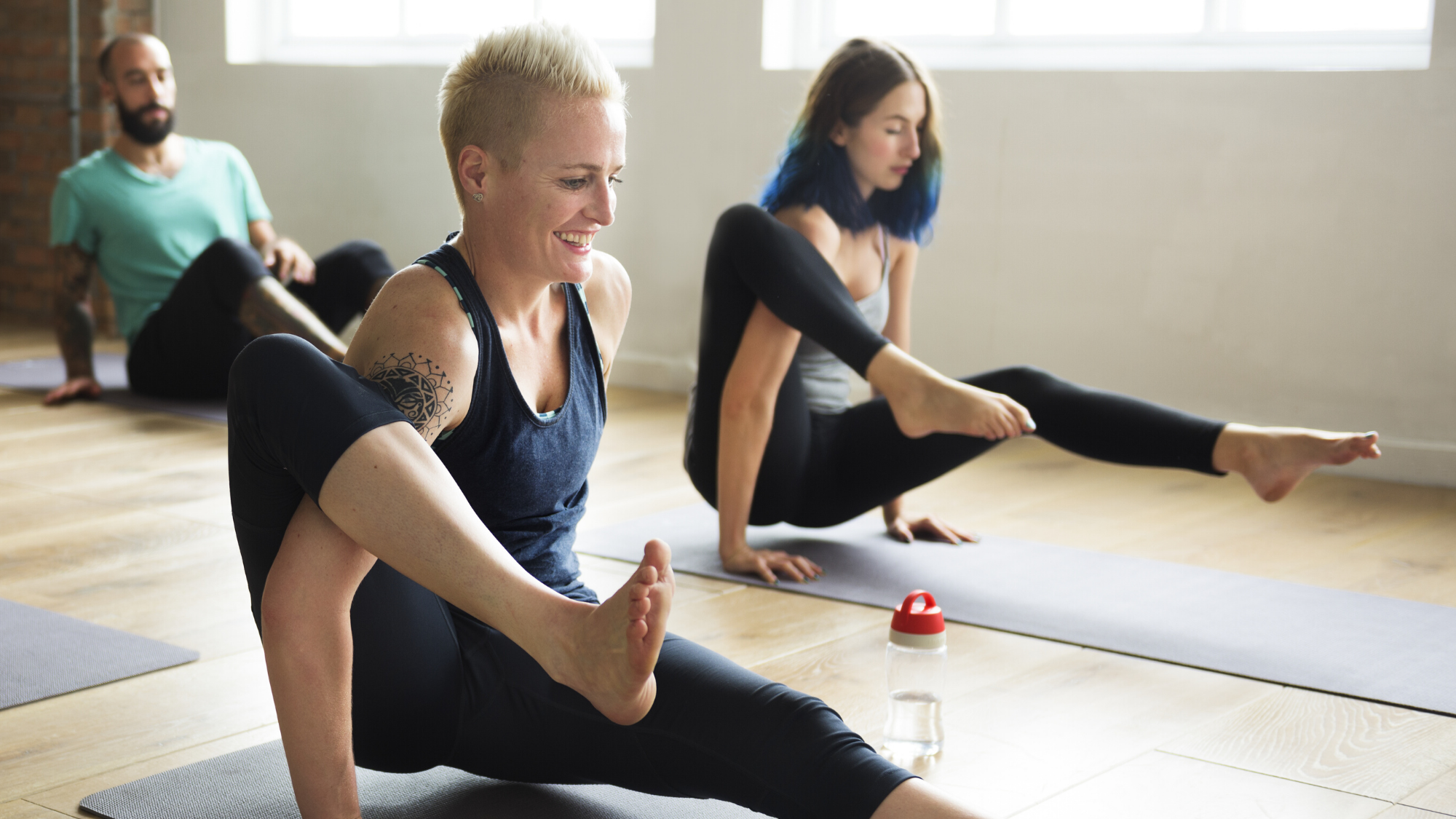 Woman practicing complicated yoga pose with diverse group of yoga students.