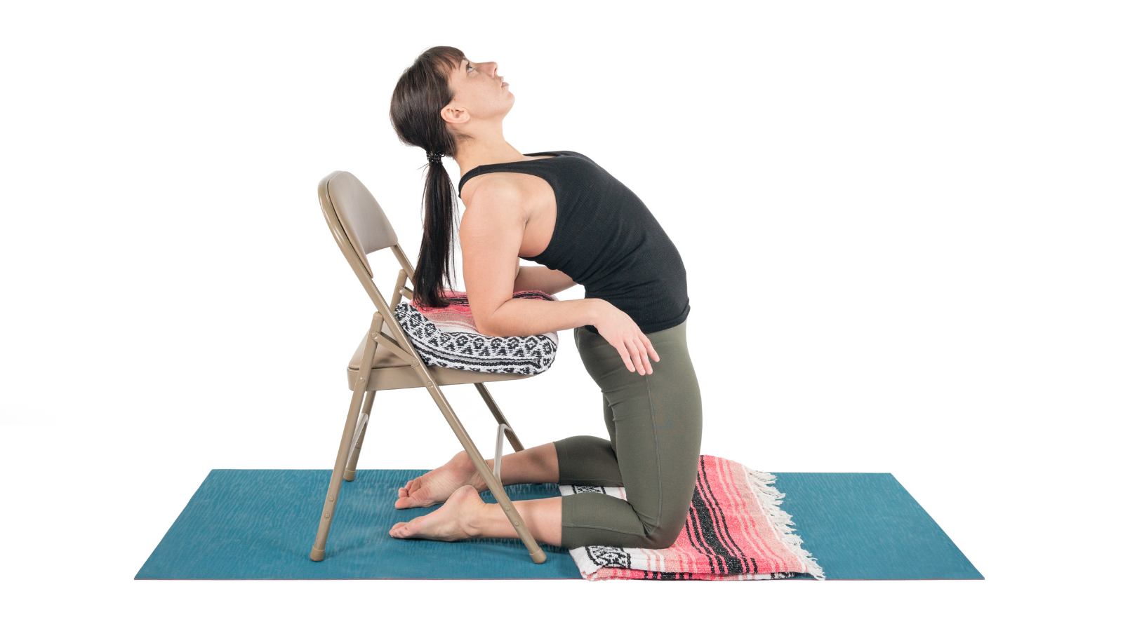 Practicing Camel Pose with the assistance of a chair and props to ease into a backbend and the opening of the heart chakra