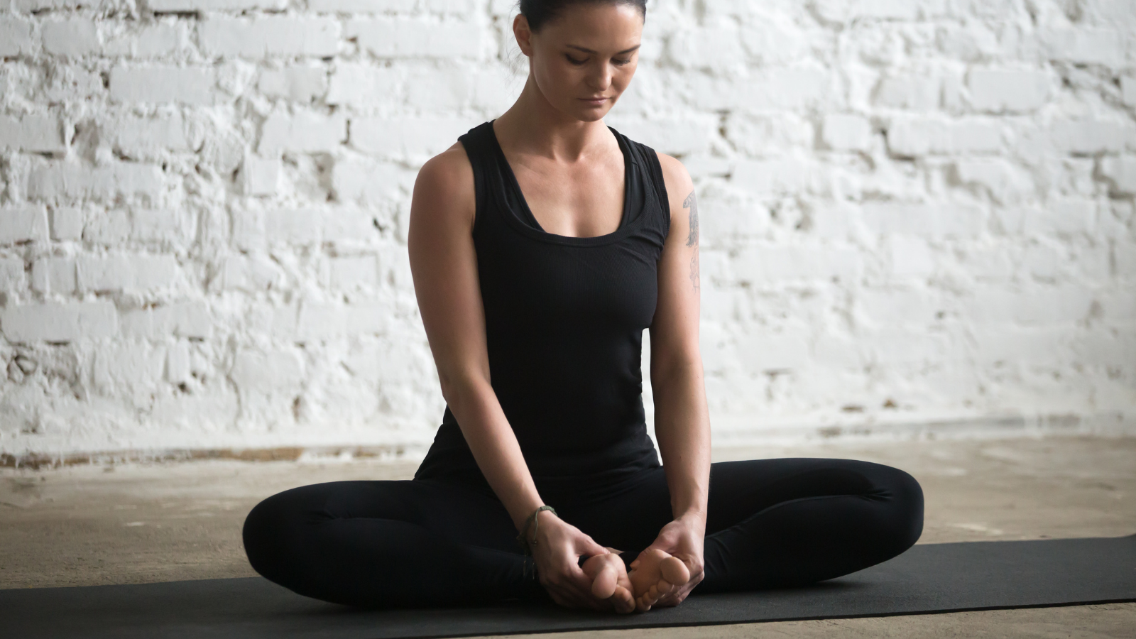Young yogi attractive woman practicing yoga concept, sitting in Butterfly exercise, Baddha Konasana pose