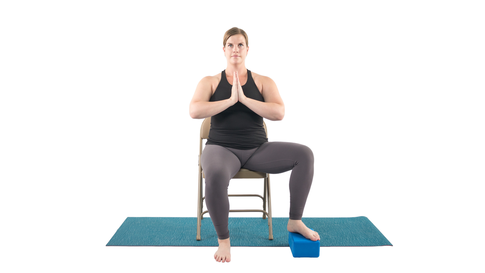Woman practicing accessible version of tree pose seated in a chair with a block for her foot.