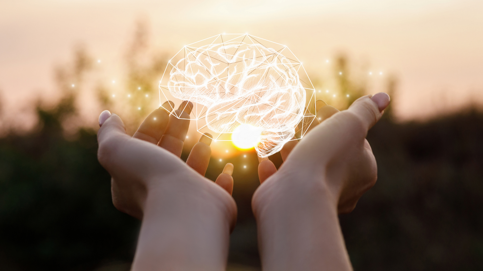 Two hands holding an illustration of a brain illuminated.