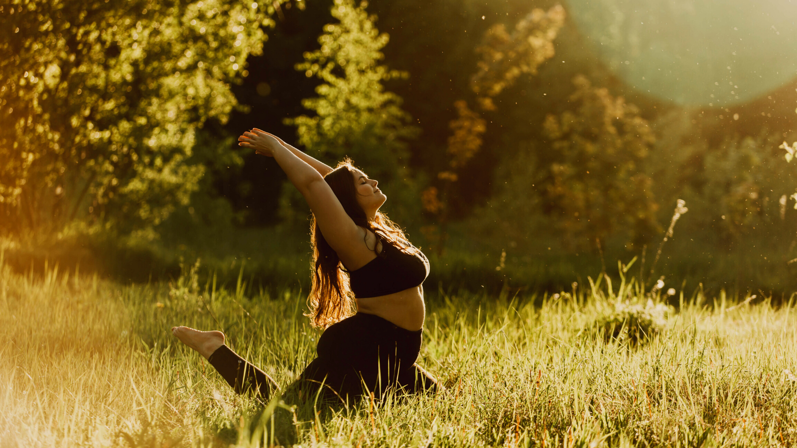 Curvy woman practicing pigeon pose in the grass.