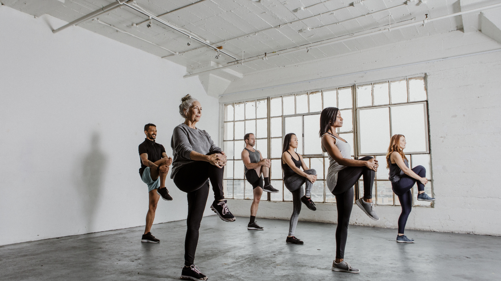 Diverse people stretching their knees and practicing balance in a yoga class