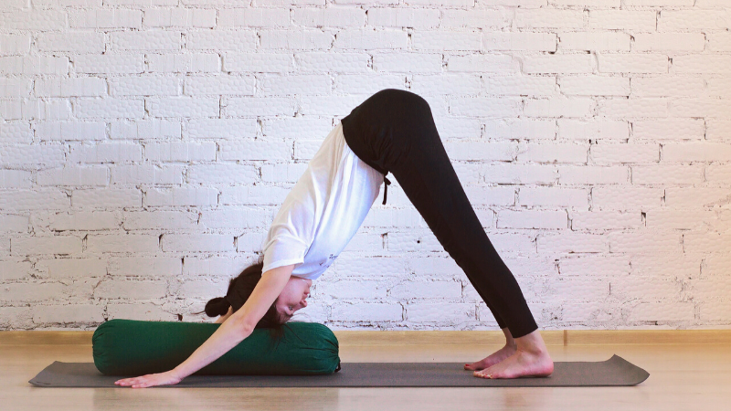 Woman practicing Downward Facing Dog with a bolster under her head