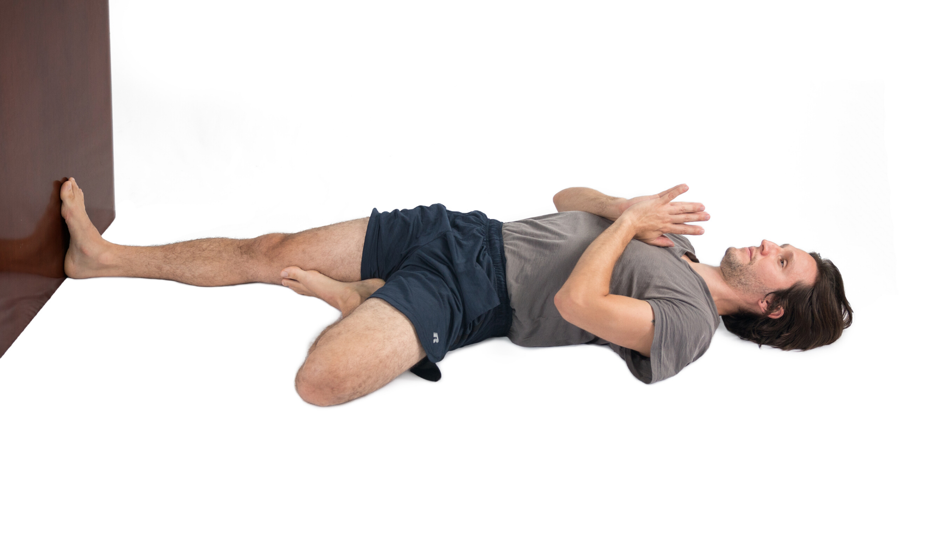 Man practicing accessible version of yoga tree pose lying on his back.