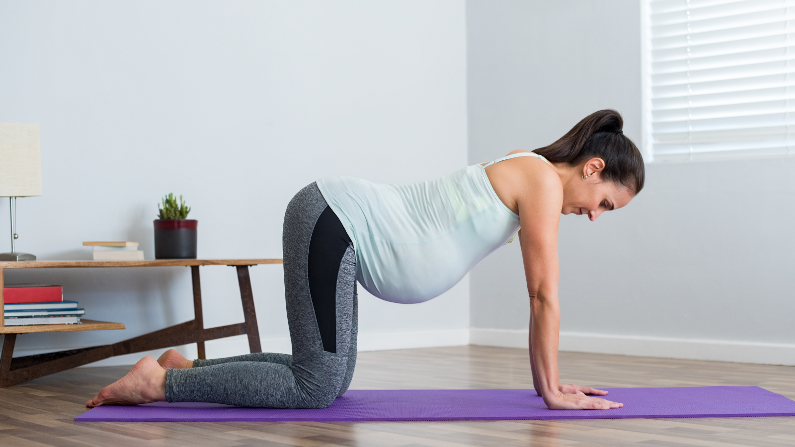 Pregnant young woman in Table Top Pose position practicing prenatal yoga to strengthen the pelvic floor