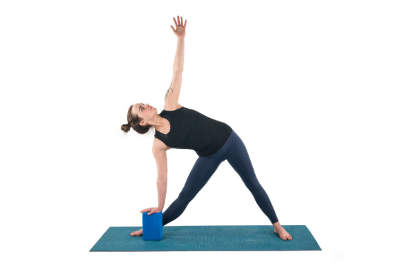 Woman practicing yoga triangle pose with a block