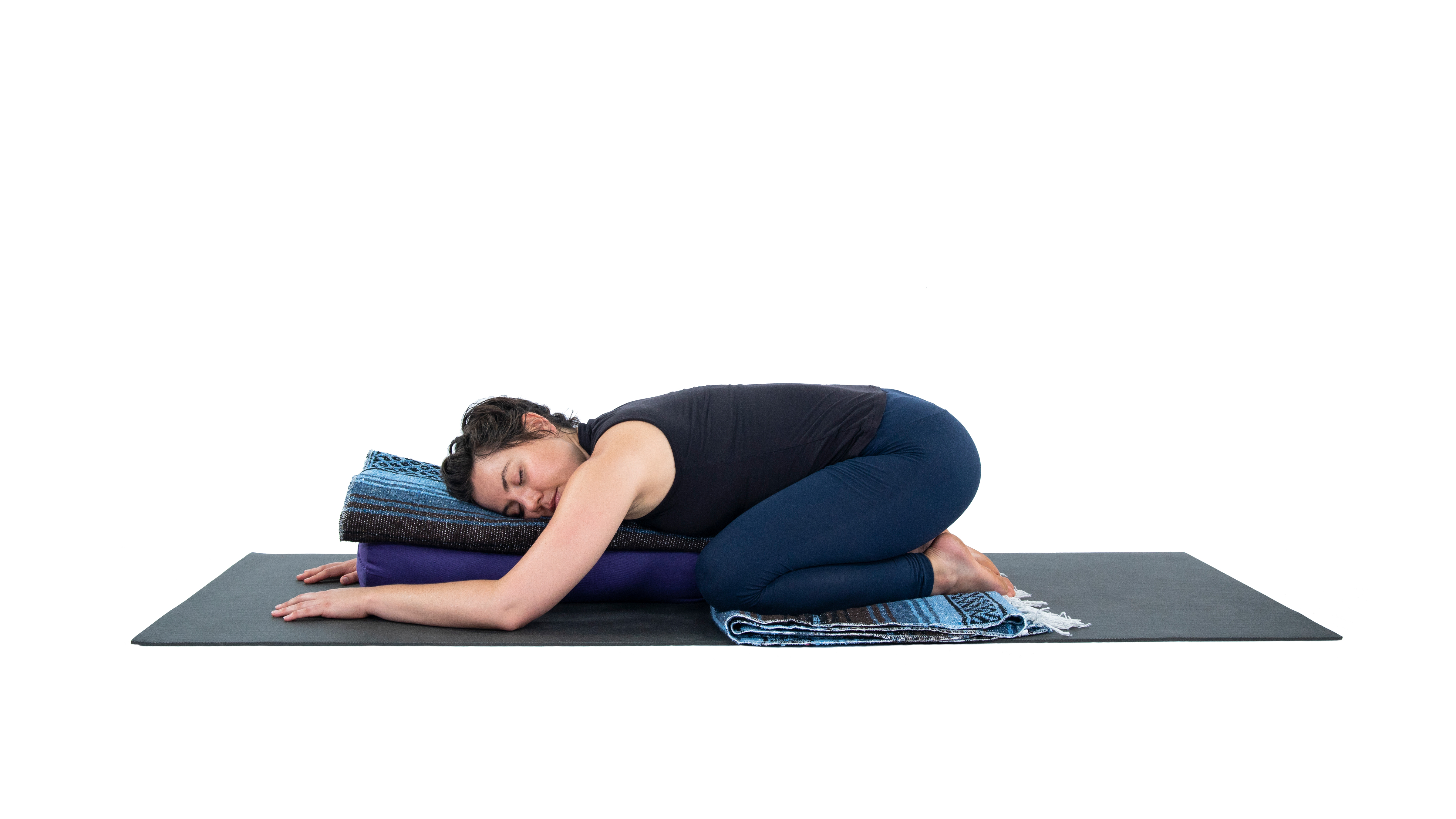 Woman in a variation of Child's Pose (Balasana) with a blanket, practicing restorative yoga