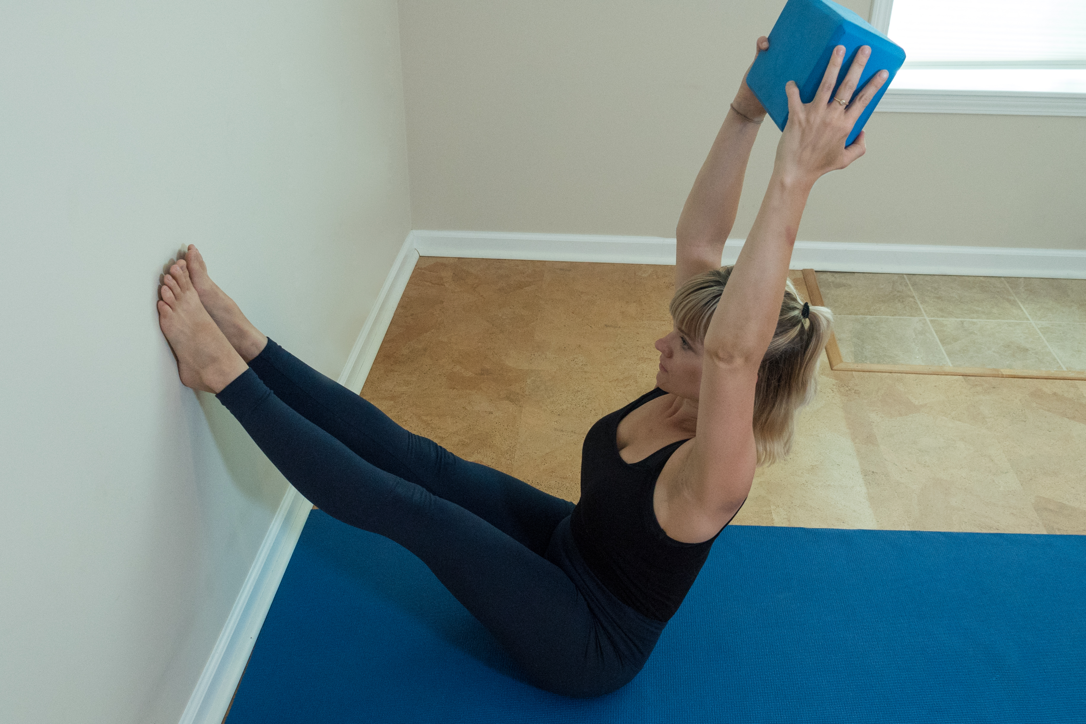 woman preparing for handstand practicing yoga boat pose