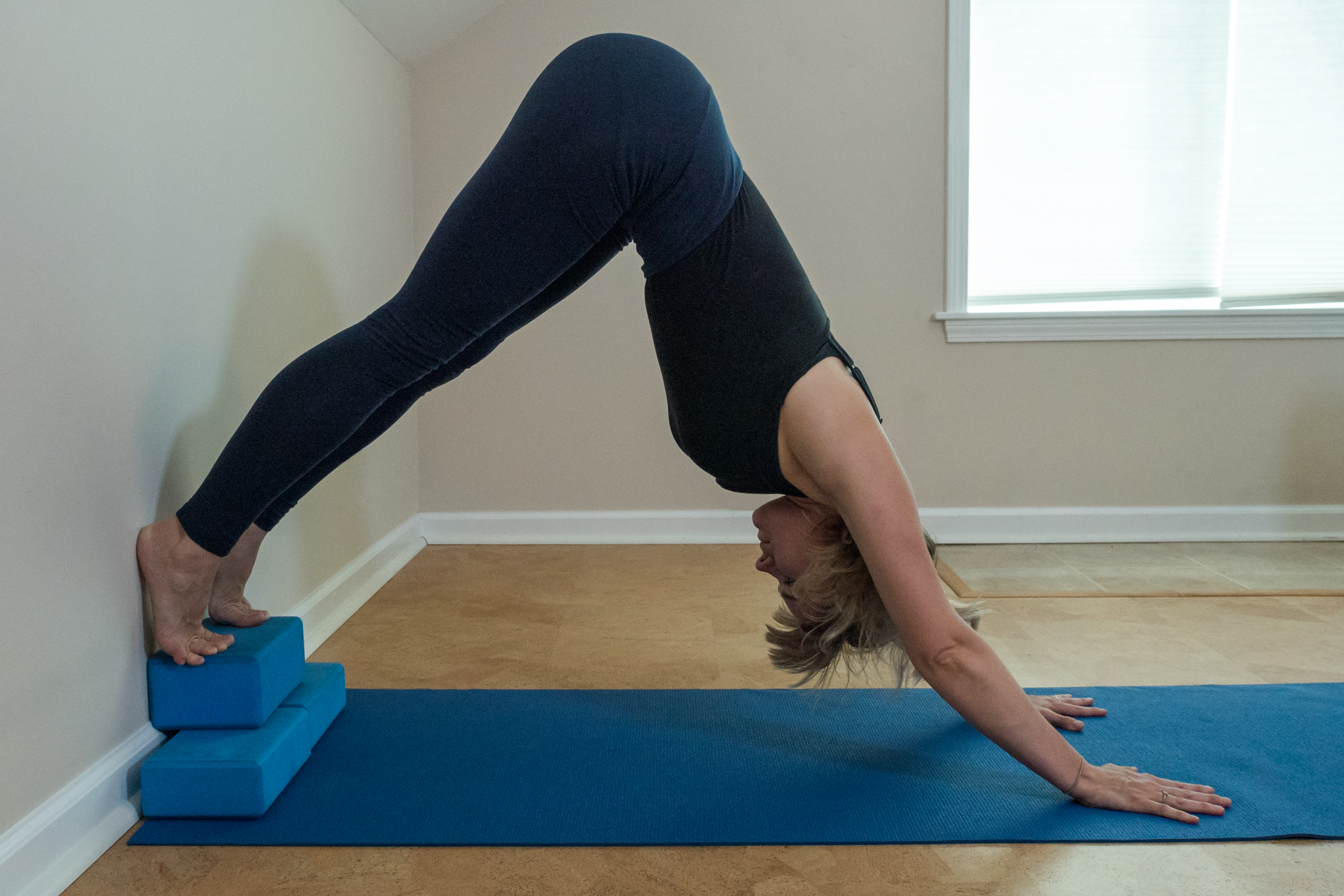 woman preparing for handstand with downward dog with heels elevated on two blocks