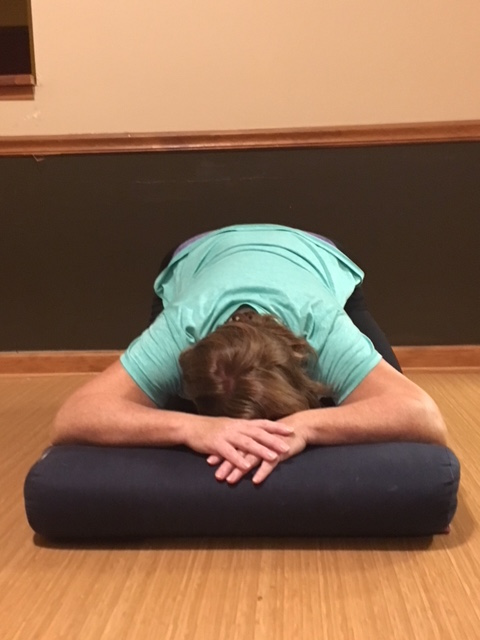 Woman in Child's Pose (Balasana) to reduce neck and head tension with a pillow, practicing restorative yoga