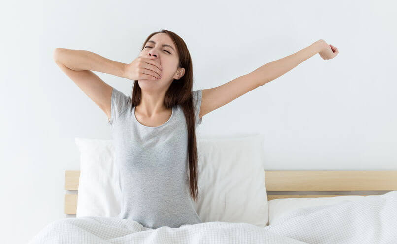Woman stretching (practicing pandiculation) as part of waking up in the morning