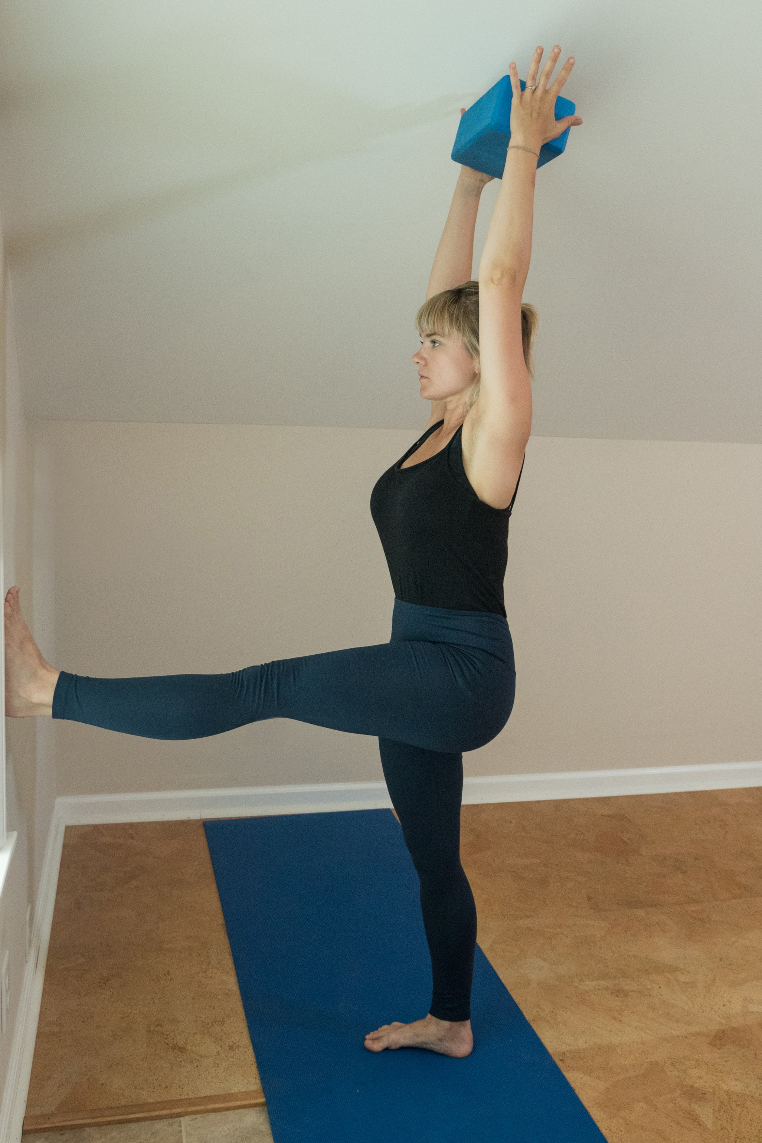 woman practicing preparation for handstand standing with arms over head in L-position with one leg on the wall