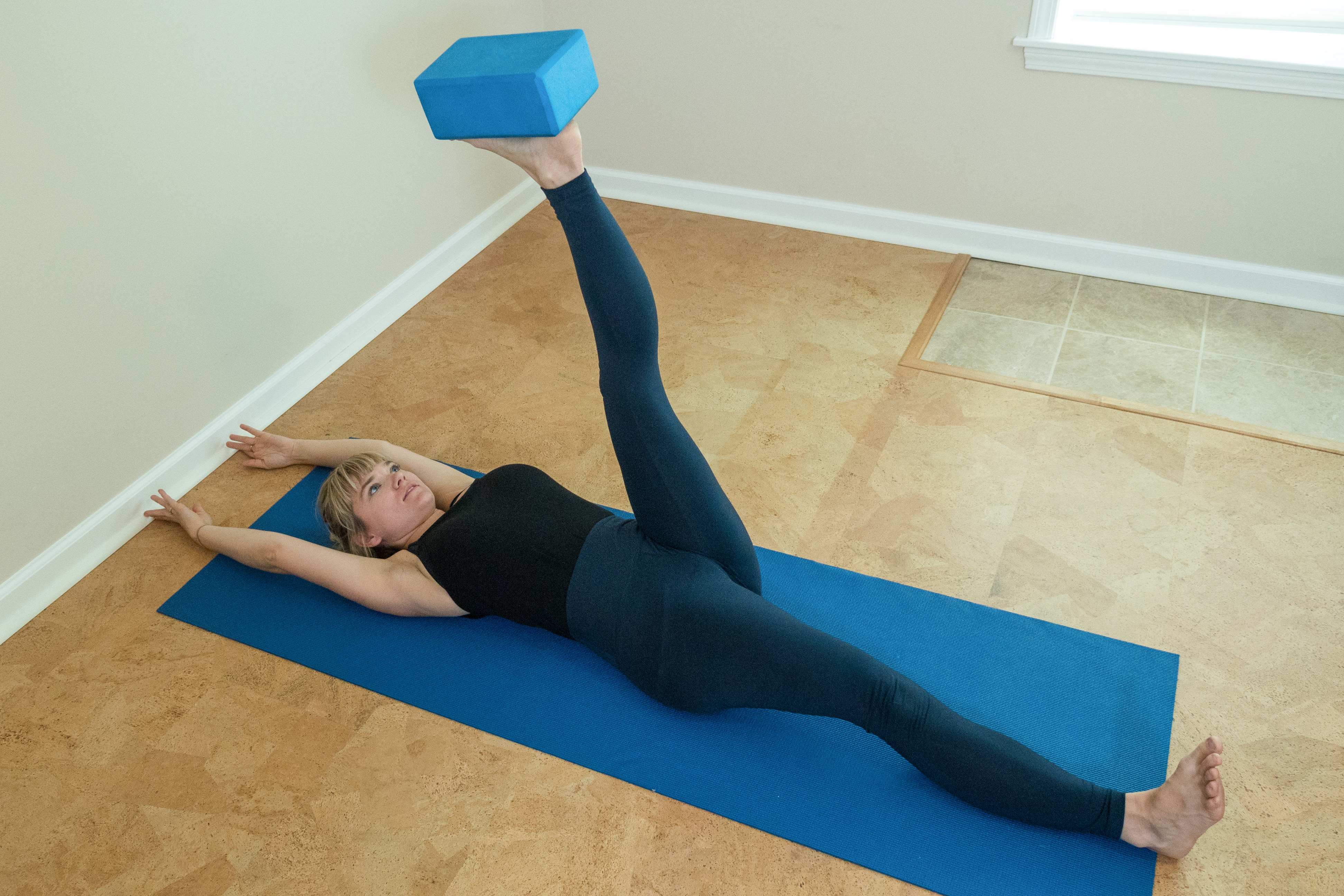 woman practicing supine half L-handstand with a block and the wall