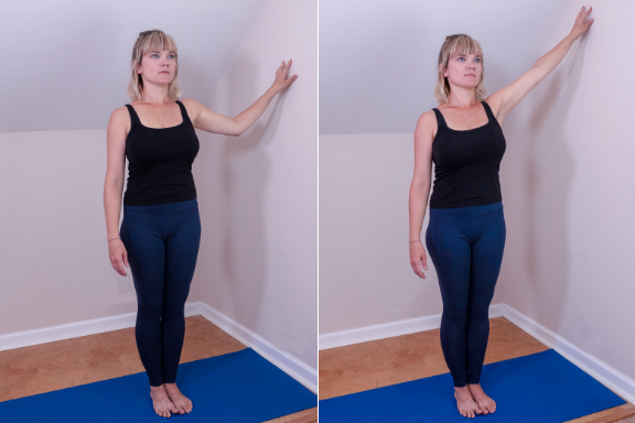 Woman practicing yoga shoulder exercise at a wall