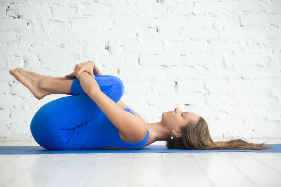 Woman practicing yoga knees to chest counterpose to backbend