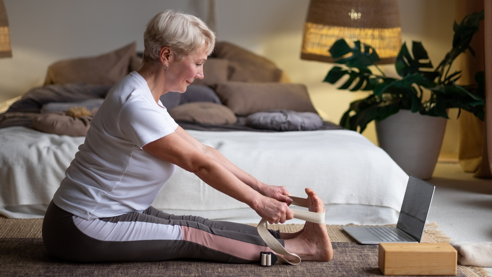 Senior caucasian woman practicing yoga sitting in Seated forward bend exercise (paschimottanasana pose) working out at home