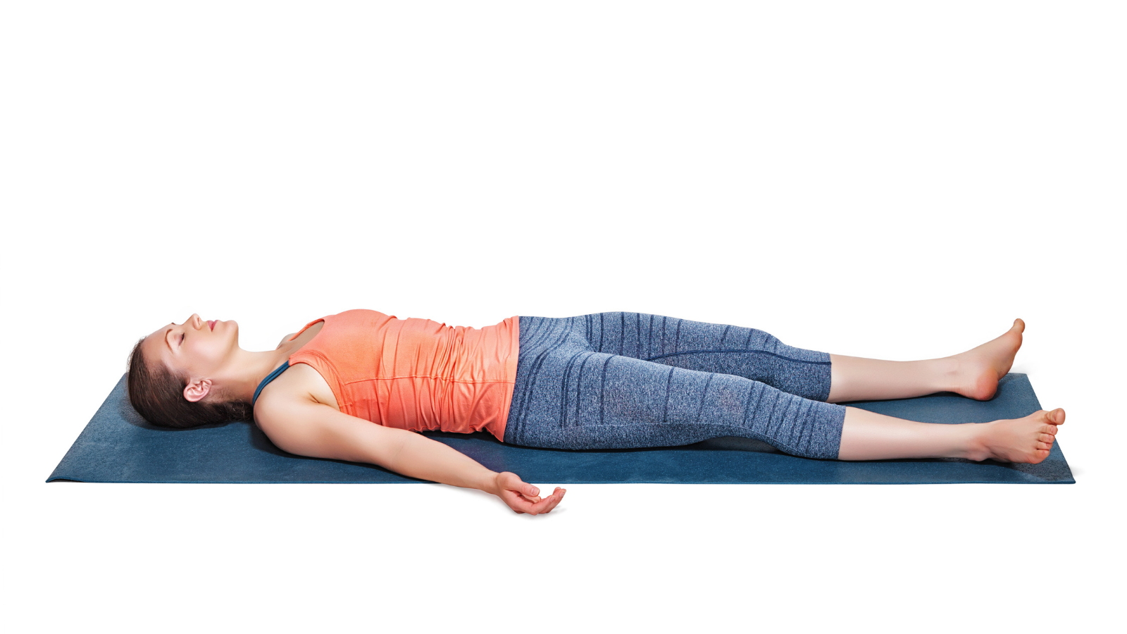 sporty fit woman relaxes in yoga's Savasana or Corpse Pose in studio