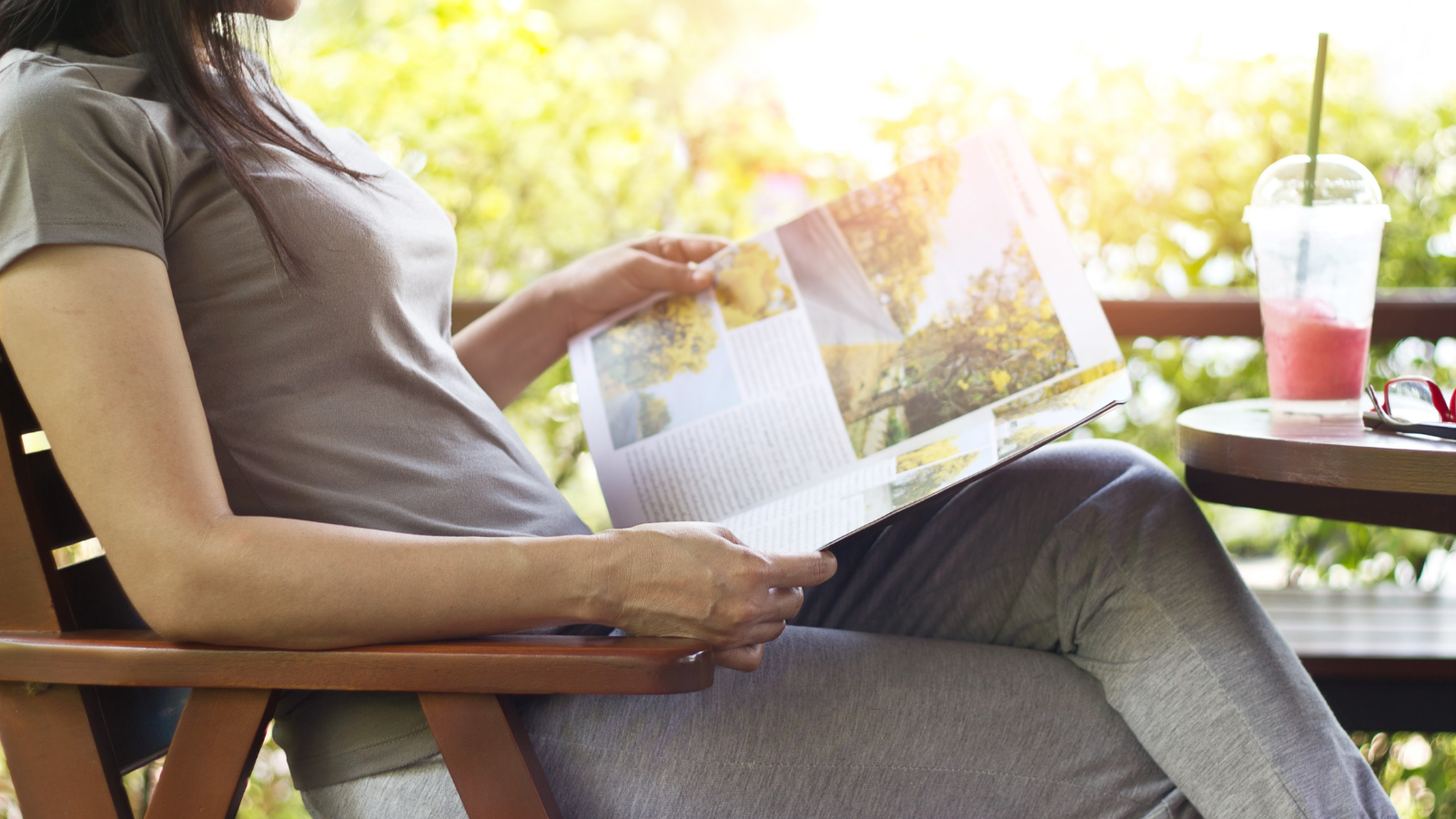 Woman relaxing by reading magazines also enjoying a strawberry smoothie