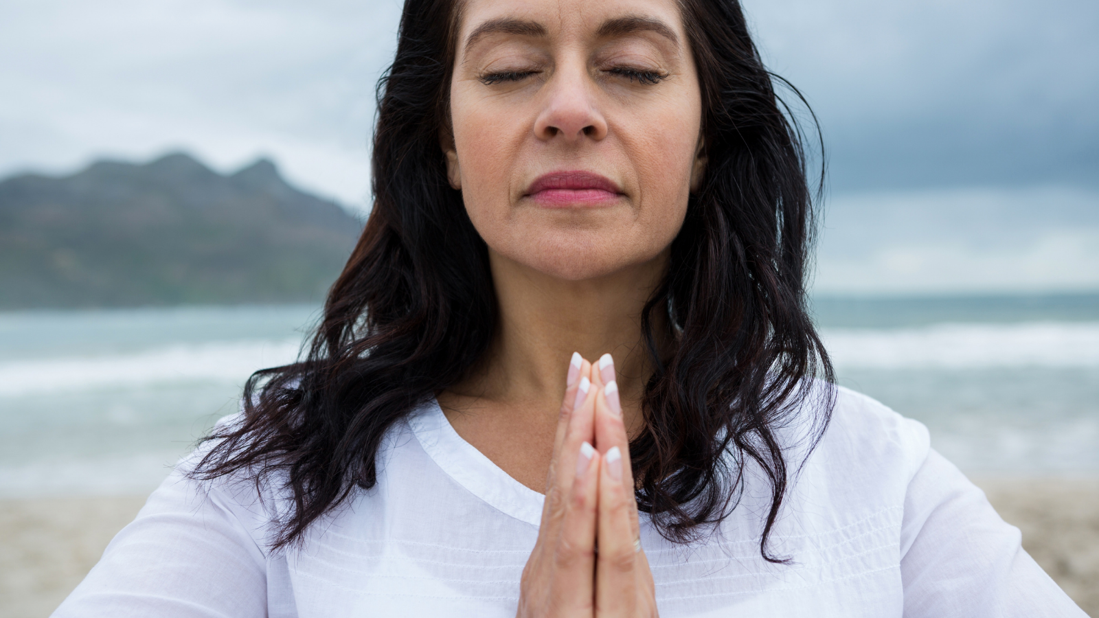 Woman in contemplative state with hands in Anjali Mudra representative of opening the heart chakra