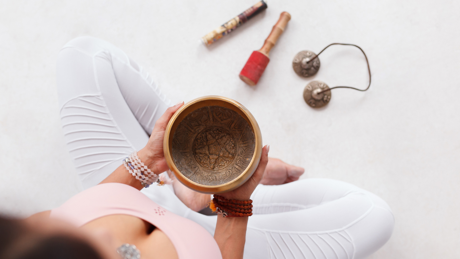 Young woman holding Tibetan singing bowl and pestle sitting on the floor next to mortar and fragrant candles for yoga and meditation