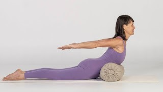 Practicing Salabhasana or Locust Pose with a Bolster to support the upper body
