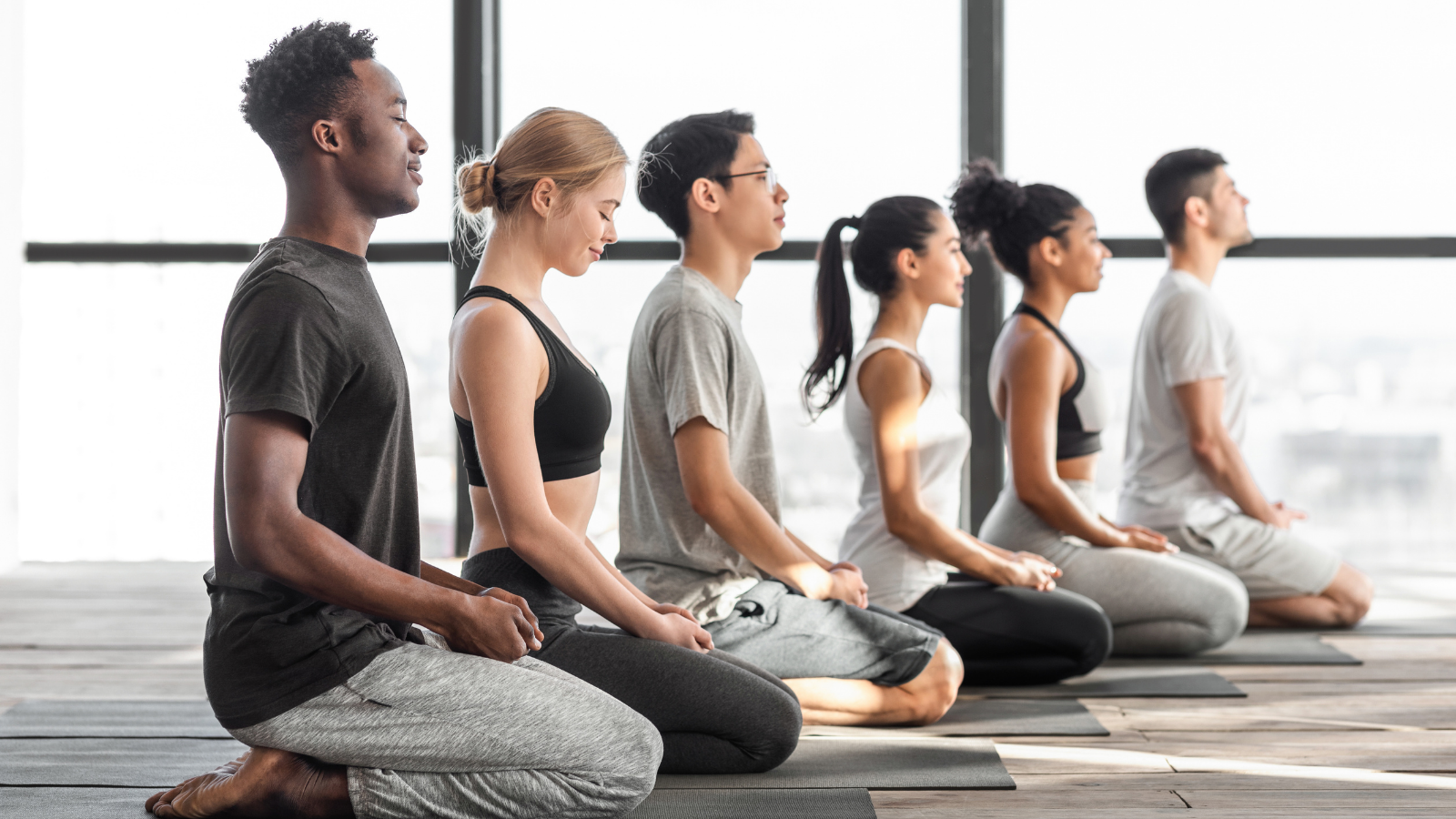 multiracial men and woman practicing yoga and meditating together in modern studio in celebration of International Yoga Day