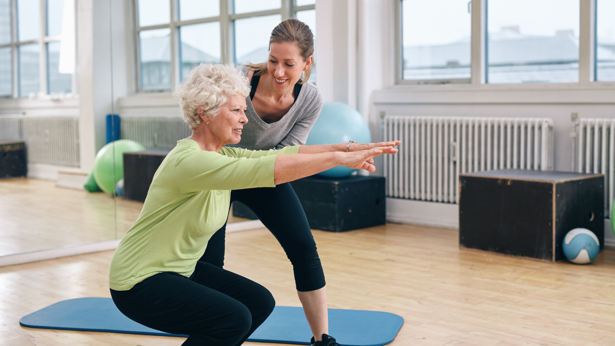Older woman being coached in yoga chair pose.