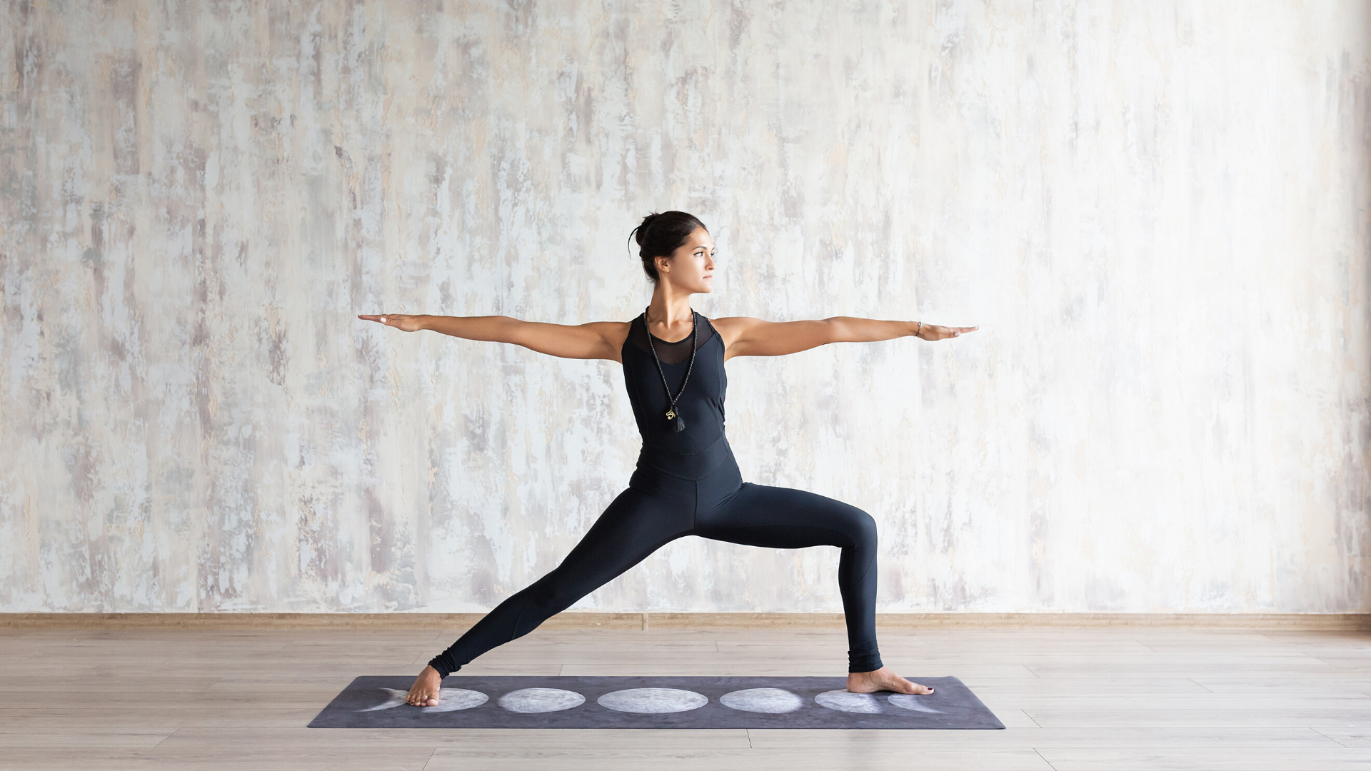 Woman practicing yoga warrior II pose at home.