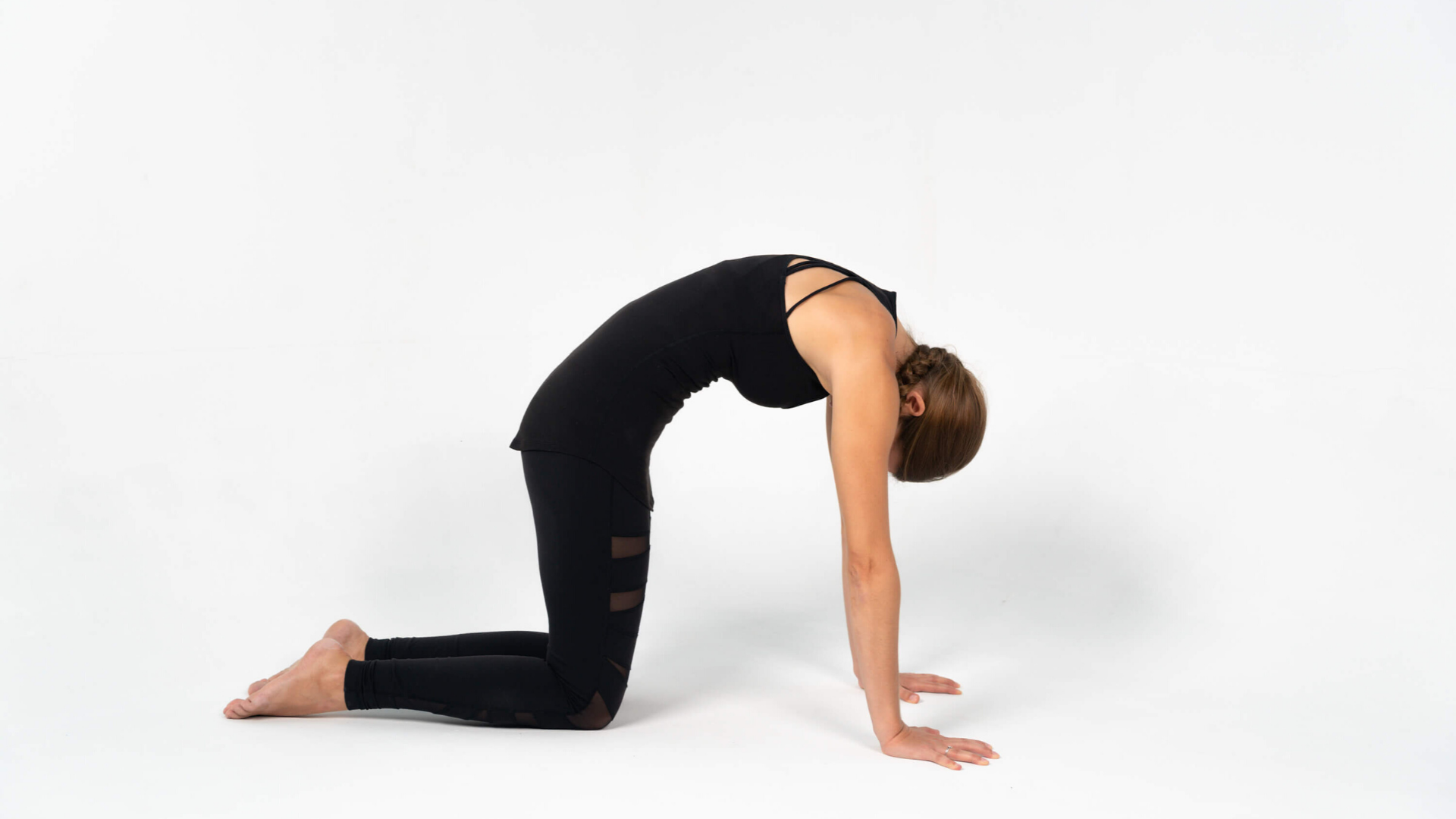 Woman practicing yoga cat cow pose marjaryasana bitilasana.