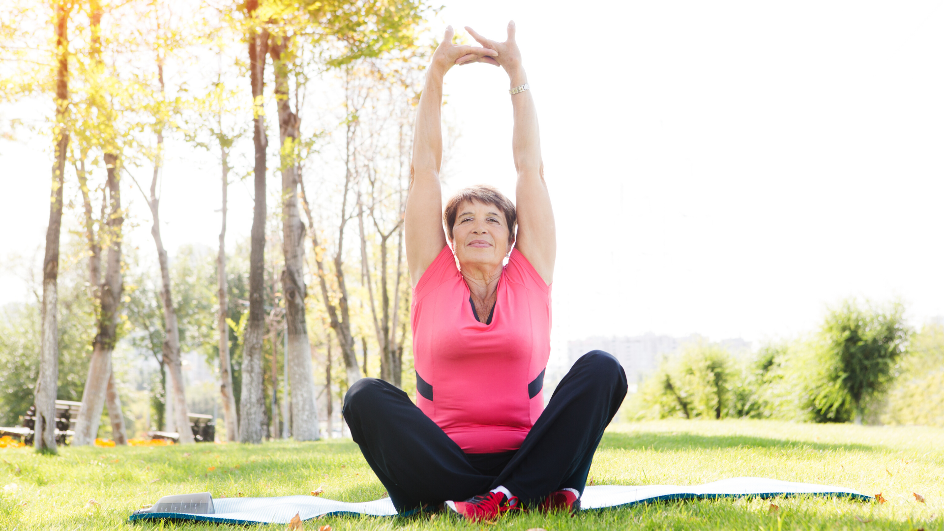 Woman practicing yoga outdoors in a park.
