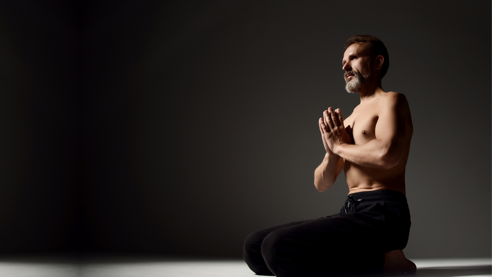 Male yoga student practicing meditation and yogic breathing pranayama.