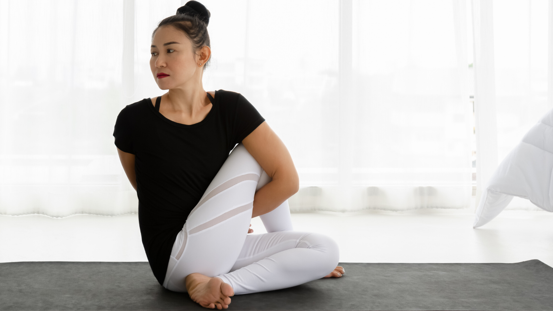 Woman practicing yoga seated twist pose.