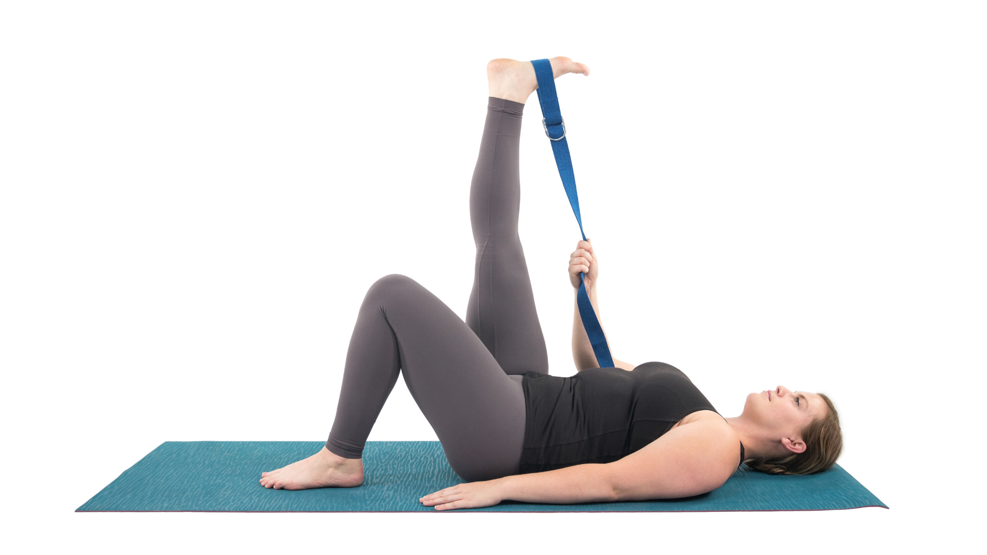 Woman practicing supta padangusthasana hamstring stretch pose.