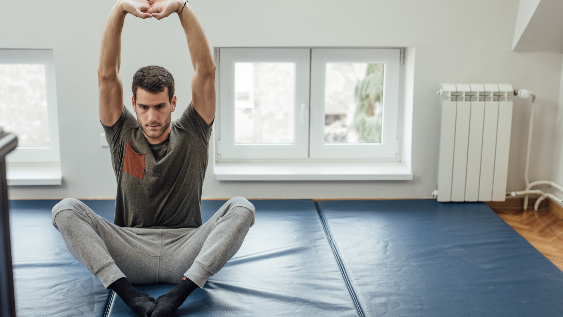 Male yoga student practicing yoga stretches at home