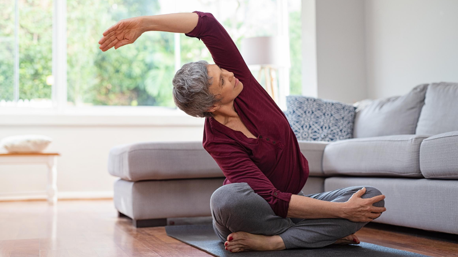 Older beginner yoga student practicing yoga for reducing symptoms of menopause