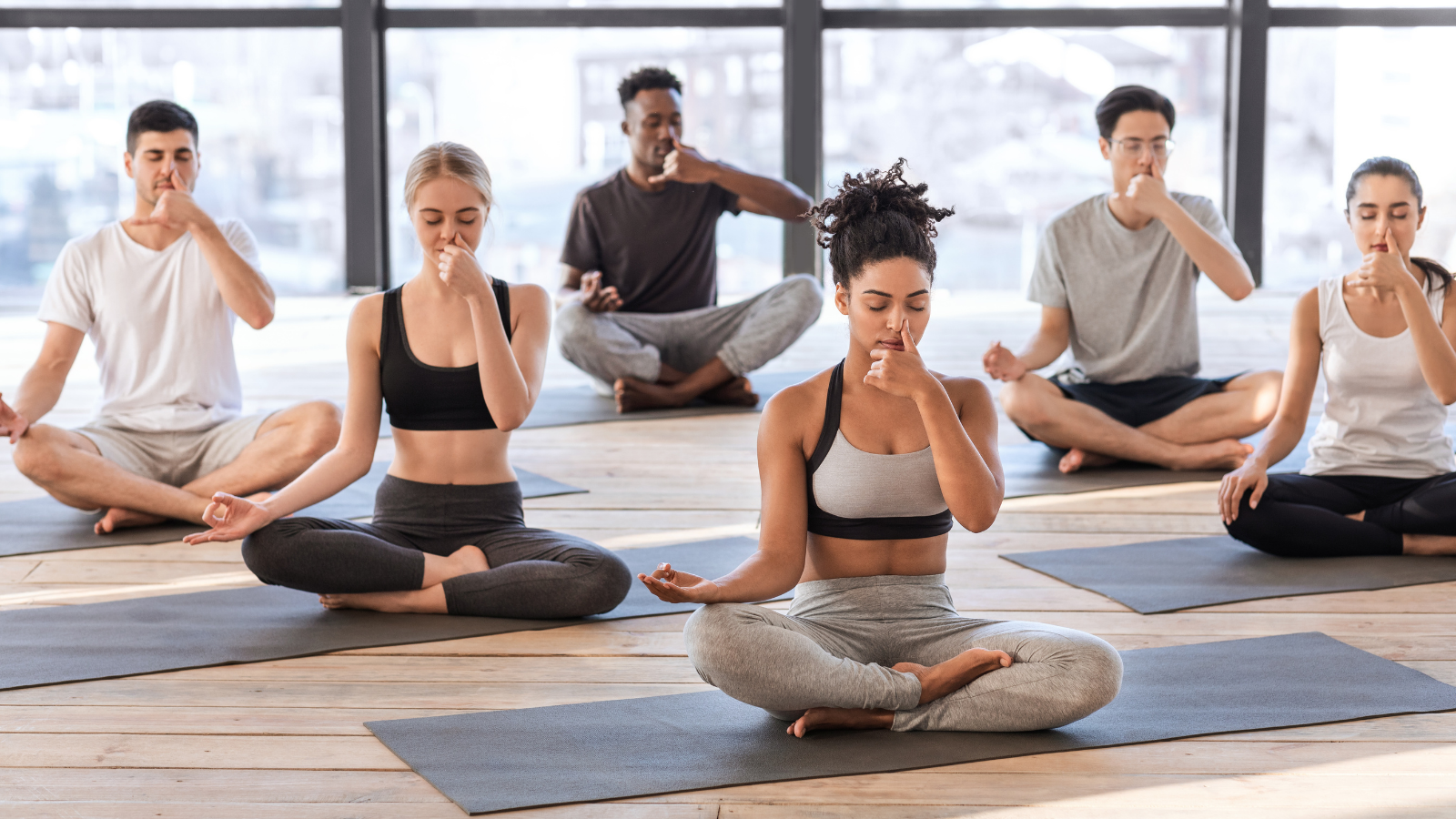 Yoga students in class practicing pranayama breathing to stimulate and balance the vagus nerve and relax