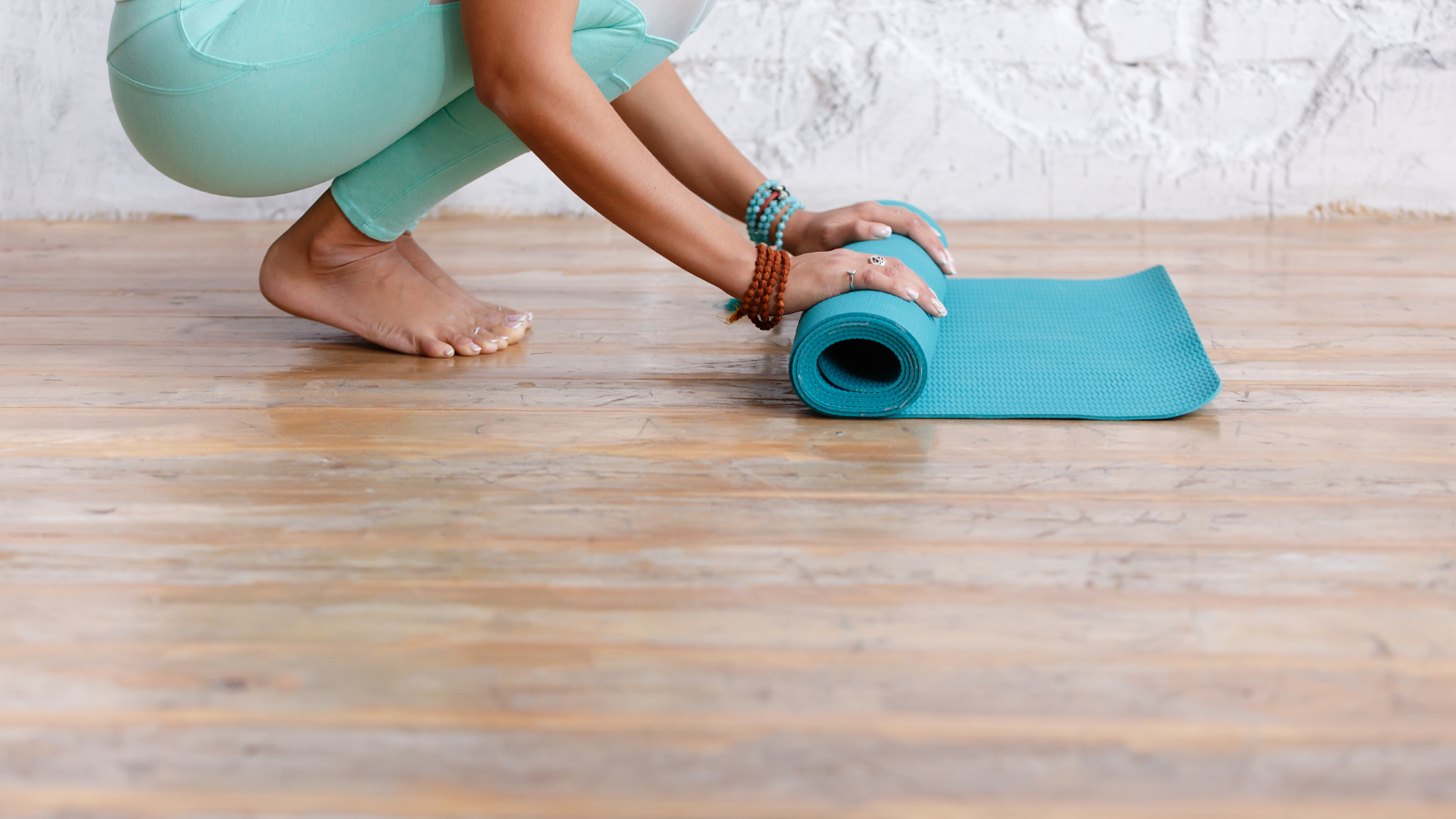 Close-up of young woman folding blue yoga or fitness mat after working out at home in living room