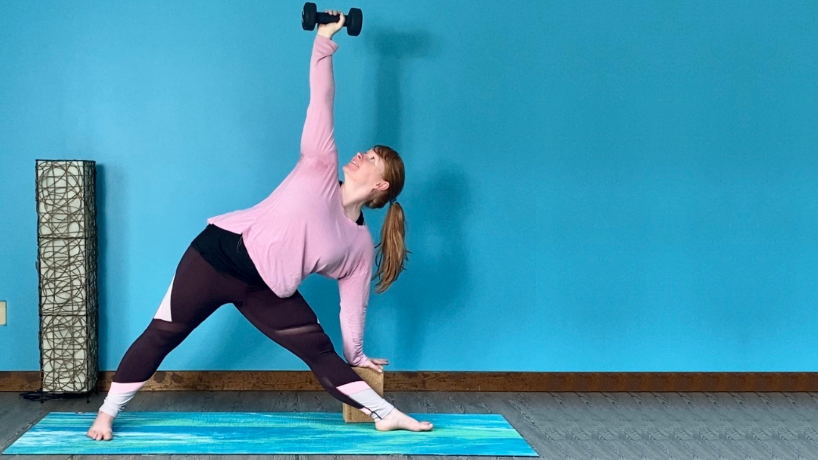 Yoga practitioner in Triangle Pose (Trikonasana) with arm weight to wake up the arms