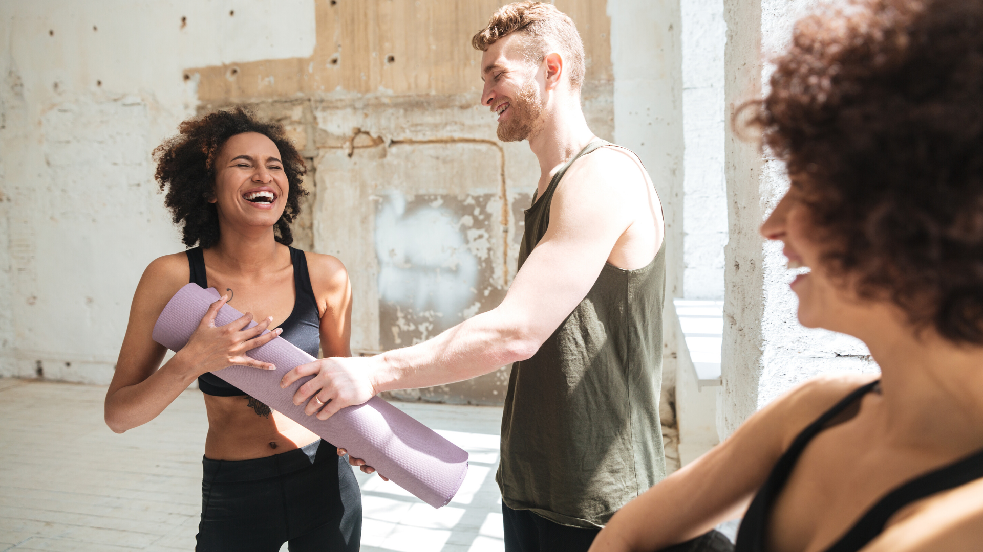 Man and woman laughing together after yoga class.