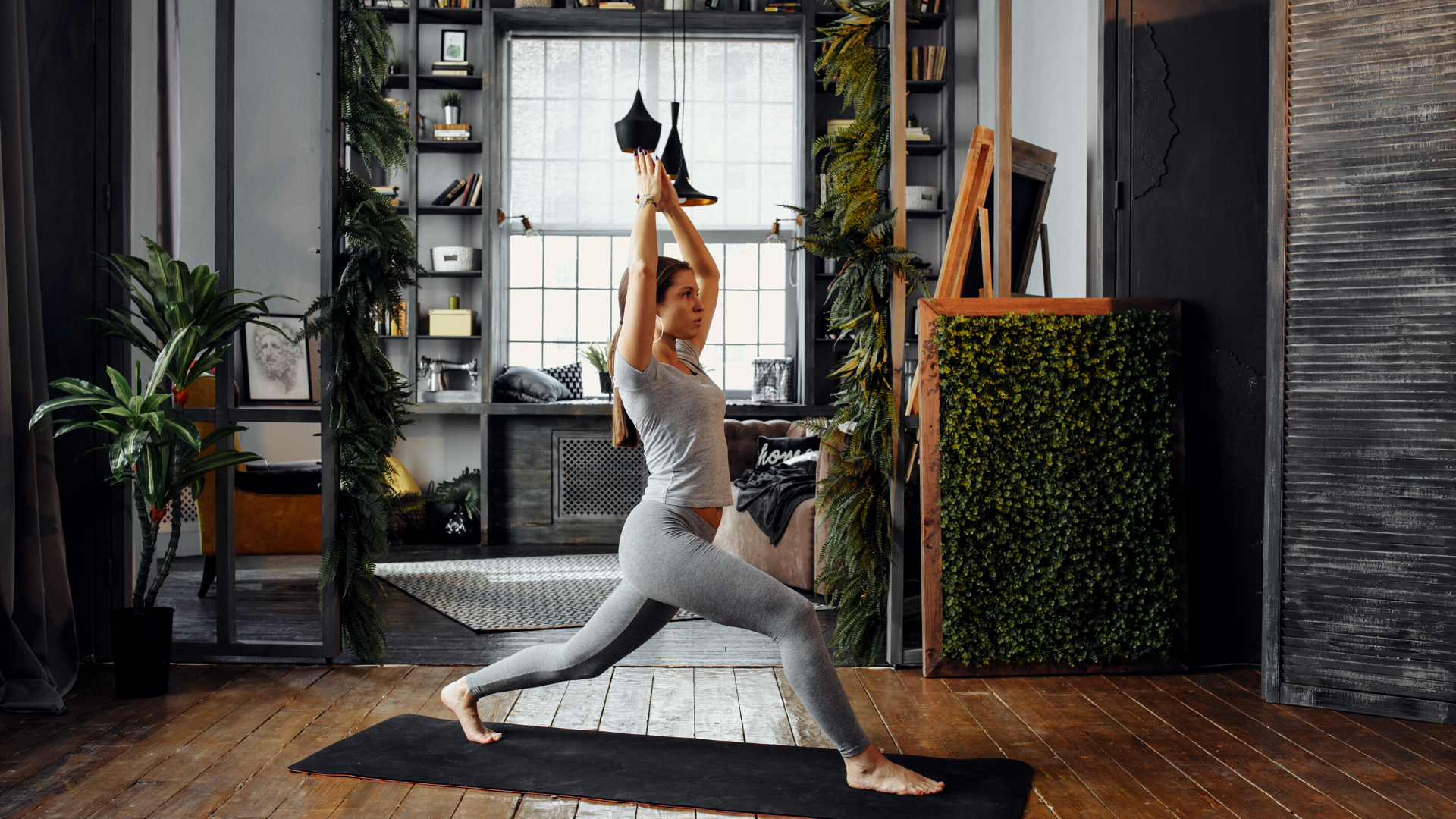 Woman practicing yoga crescent lunge pose at home.
