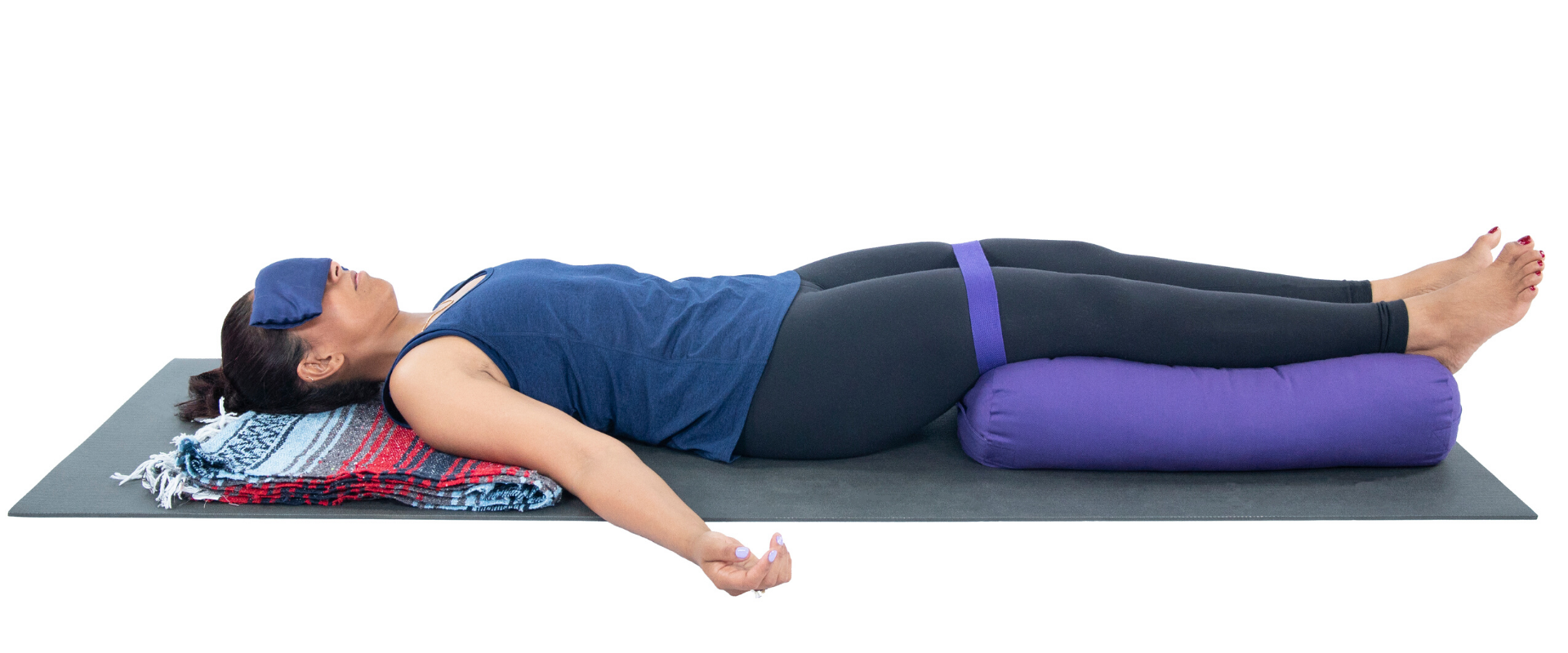 Woman practicing yoga savasana with leg support.