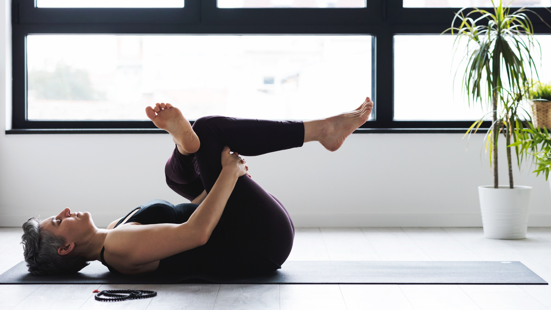 Female yoga student practicing practicing reclining pigeon pose.
