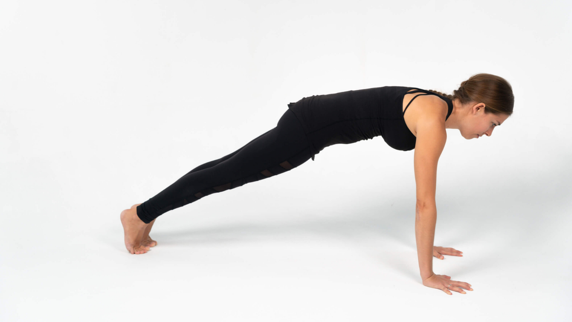 Woman practicing yoga plank pose phalakasana.