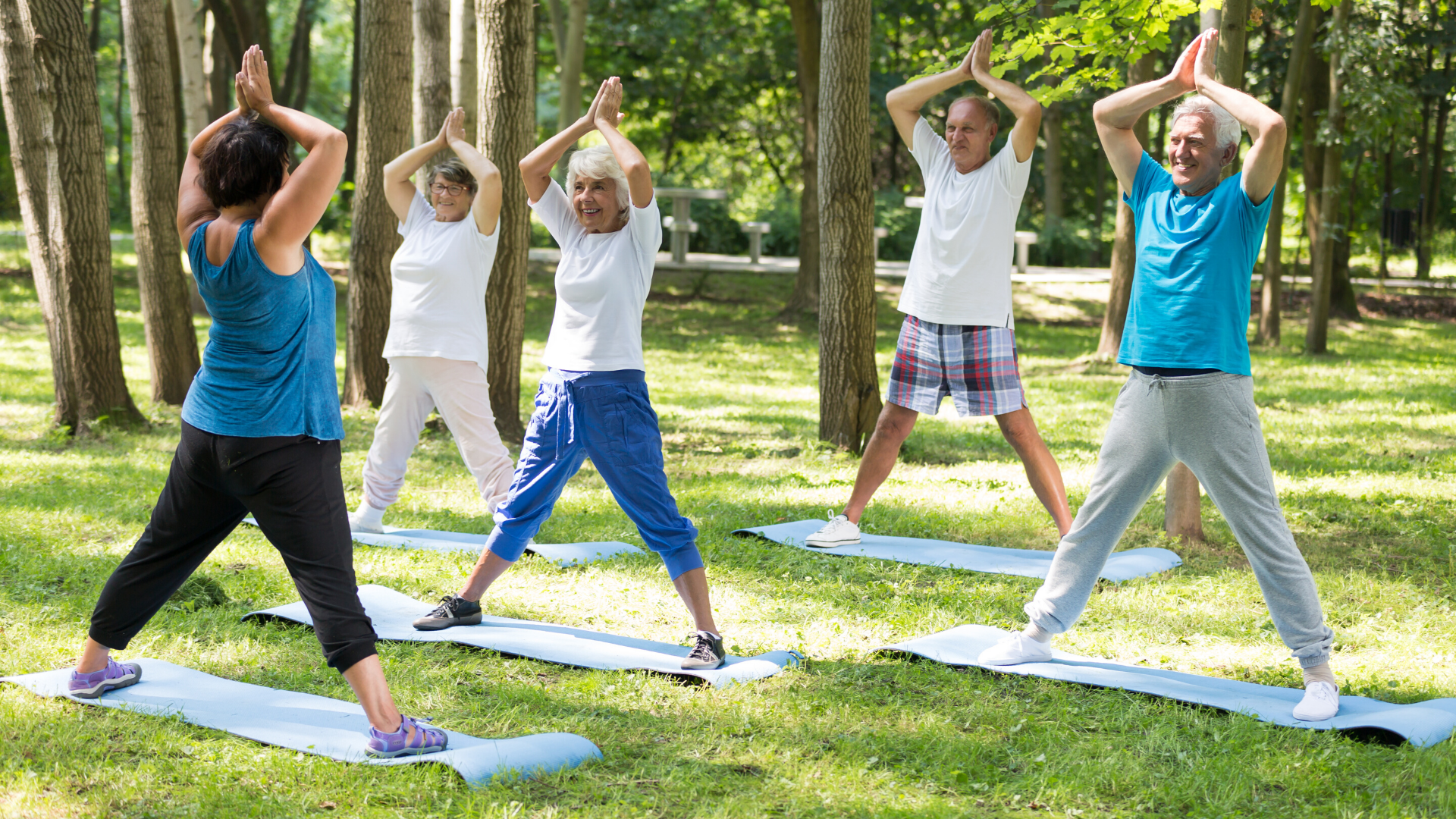 Group of older yoga students practicing yoga outdoors.