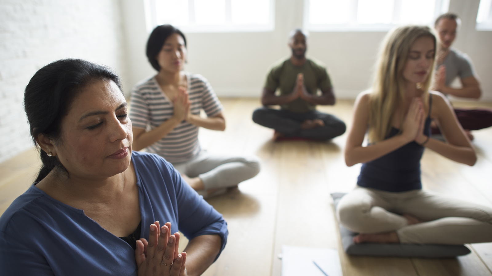 Group of diverse yoga students practicing meditation.