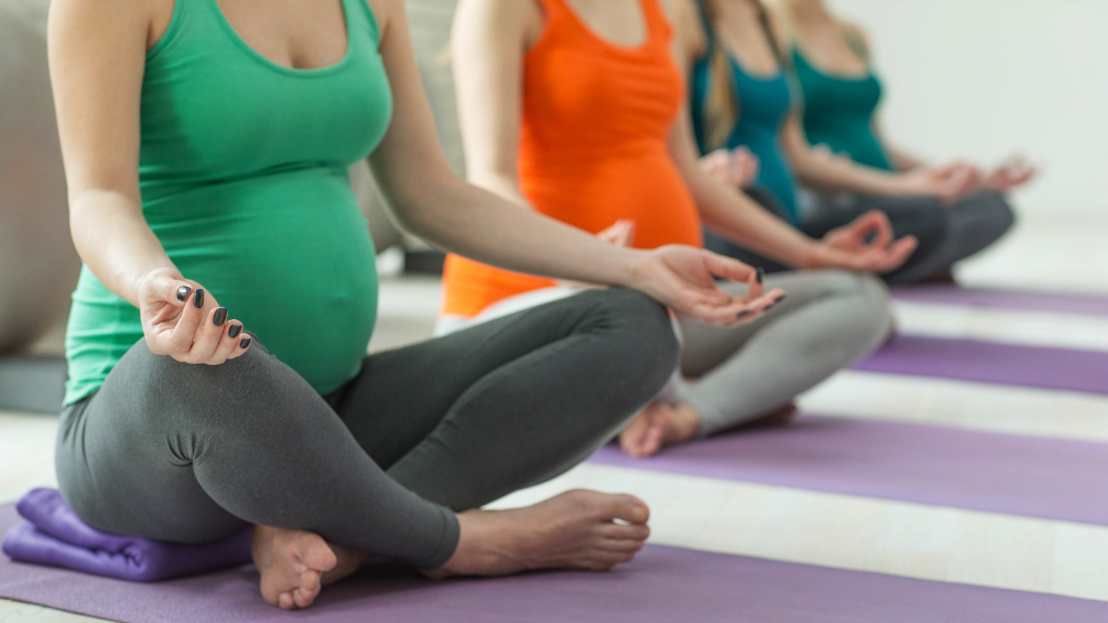 Prenatal yoga class for pregnant people practicing safely while listening to their bodies