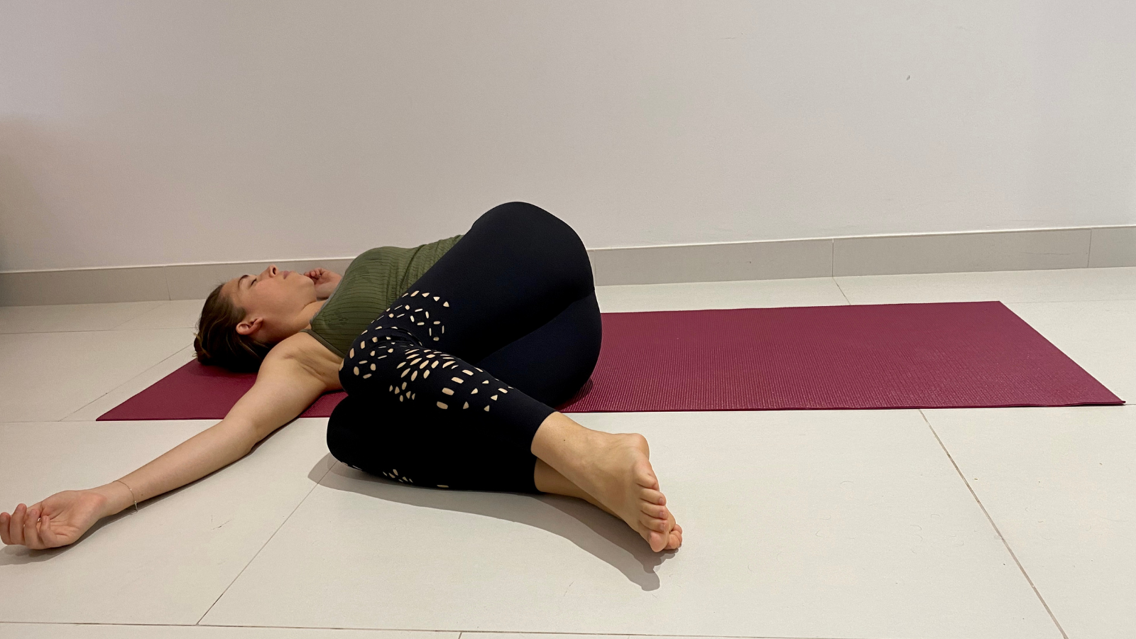 How to practicing twisting spine yoga poses in Revolved Belly Pose (Jathara Parivrttanasana) to ease back pain
