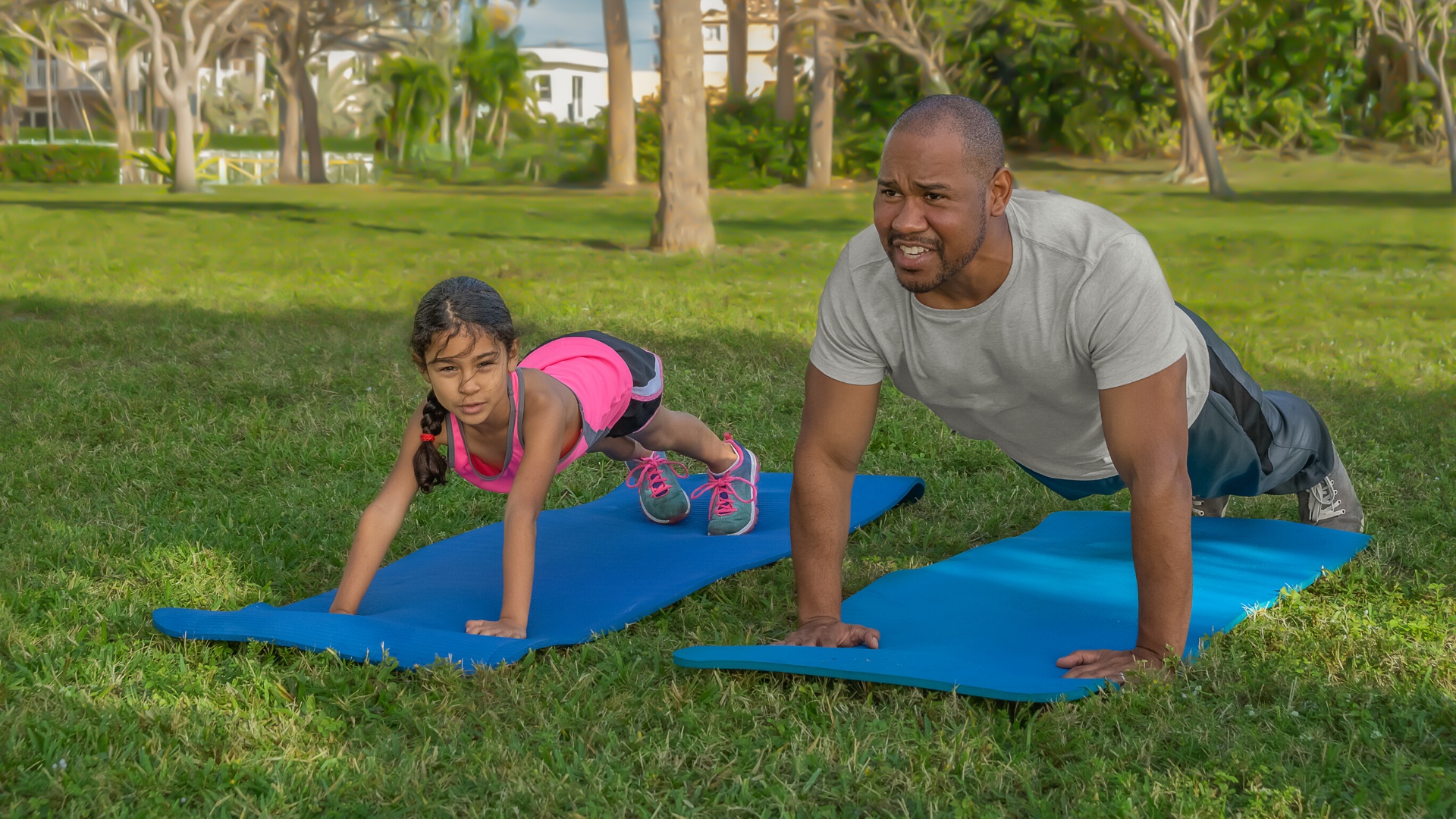 family of yoga students practicing plank pose in yoga outside