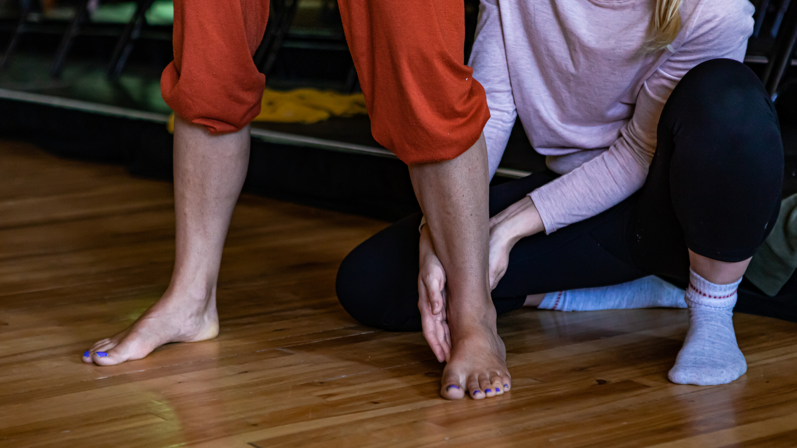 Yoga teacher adjusting student's stance in yoga class